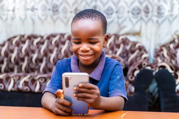 座って微笑んでデジタル電話を使用してインターネットを閲覧している若いスマートな黒人アフリカの少年。技術コンセプト