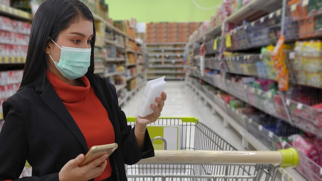 Young smart business asian woman shopper with face mask choosing grocery to buy from shelf in supermarket department store or shopping mall, new normal coronavirus crisis or covid19 outbreak.
