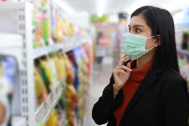 얼굴 마스크를 쓴 젊고 똑똑한 아시아 여성은 슈퍼마켓 백화점이나 쇼핑몰, 새로운 정상 코로나바이러스 위기 또는 covid19 발병에서 식료품을 찾고 선택합니다.