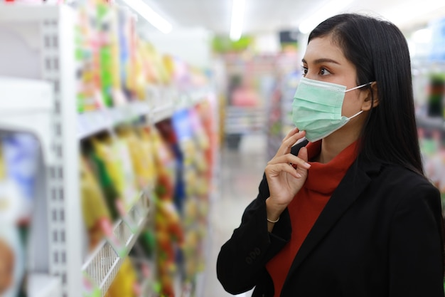Young smart business asian woman wearing face mask looking and choosing grocery to buy from shelf in supermarket department store or shopping mall, new normal coronavirus crisis or covid19 outbreak.