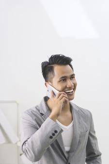 彼のスマートフォンで話している若いスマートビジネス男