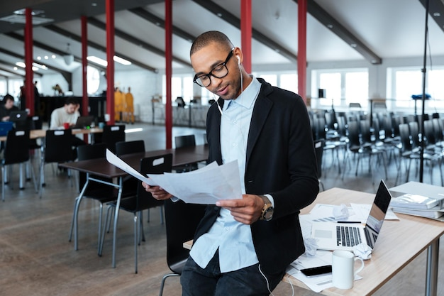 Молодой умный бизнесмен просматривает документы в офисе