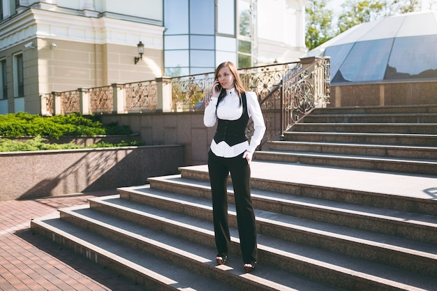 Young smart businesswoman in classic suit, shirt talking on mobile phone. beautiful brunette woman standing on stairs near building outdoors. mobile office female worker. freelance business concept.