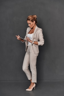 Young and smart. full length of confident young woman in smart casual wear working on digital tablet while standing against grey background