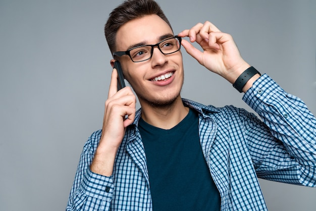 Young smart guy talks on phone, adjusting glasses