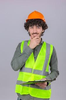 孤立した白い背景の上に立っている笑顔彼のあごに触れる若いスマート探しパン粉ハンサムエンジニアワーカー