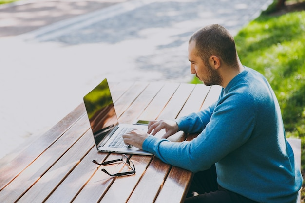 Young smart man businessman or student in casual blue shirt glasses sitting at table with mobile phone in city park using laptop working outdoors on green background. mobile office concept. side view.