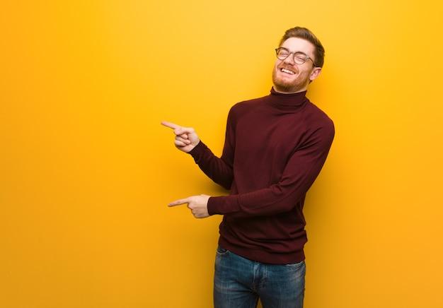 指で横を指している若い賢い男