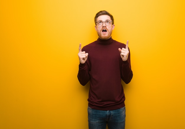 Young smart man surprised pointing up to show something