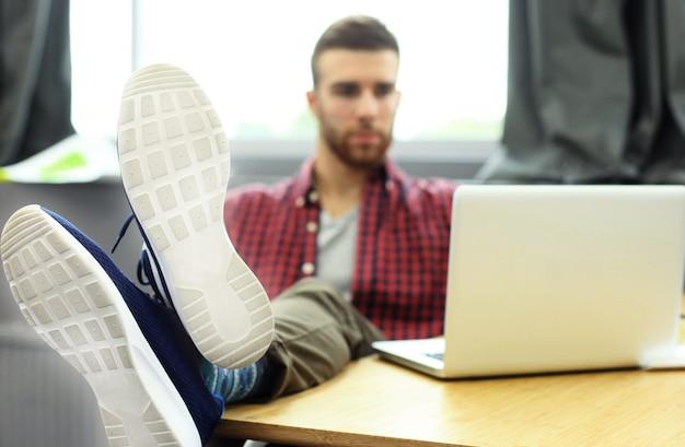 Молодые умные люди используют гаджеты, усердно работая в современном офисе. молодой человек работает на своем ноутбуке.