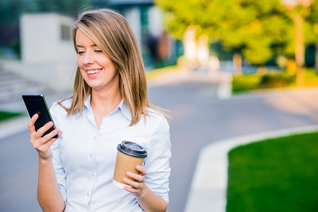 Young smart professional woman reading using phone. female businesswoman reading news or texting sms on smartphone while drinking coffee on break from work.