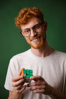 Young smart readgead bearded man in glasses, playing with rubic's cube