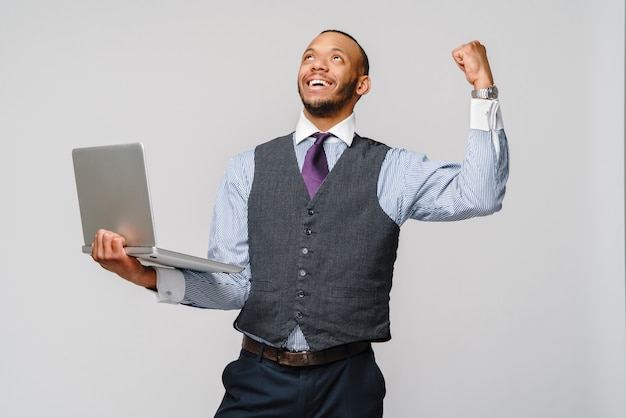 Young smart shouting african-american businessman doing success gesture and holding laptop