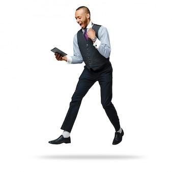 Молодой умный кричащий бизнесмен афроамериканца скача и делая жест успеха.