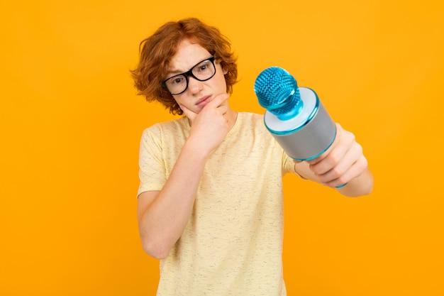 Молодой умный думая рыжий парень ведет в футболке и очках на желтом