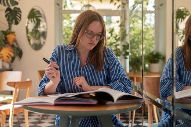 Молодая умная женщина, держащая ручку и готовящаяся к экзамену, изучает что-л. в современном кафе, студент с кучей ...