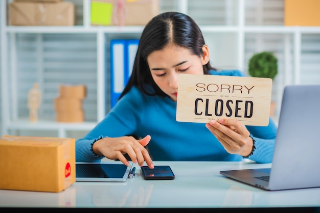 Young sme business owner startup feeling unhappy holding closed sign.