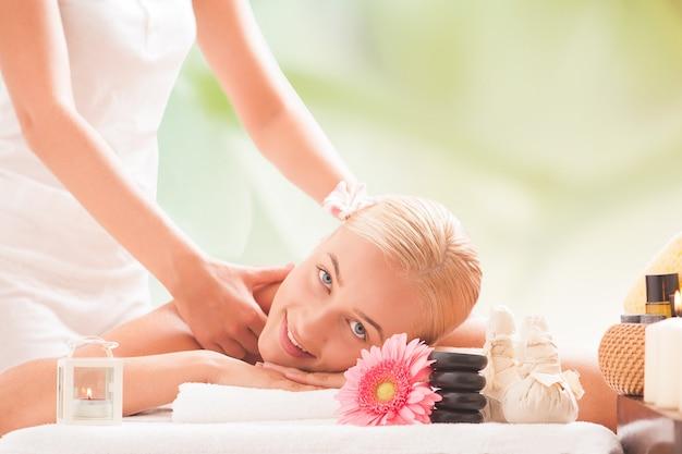 Молодая улыбка красивая блондинка женщина лежа на массажном столе и массаж.