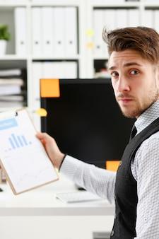 オフィスのワークスペースのクローズアップの肖像画で若い笑顔の男。