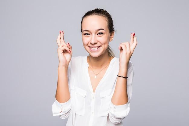 Молодая улыбающаяся женщина держит пальцы скрещенными, надеясь на удачу, изолирована от серой стены с копией пространства