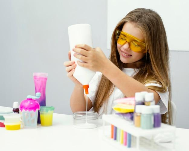 실험실에서 점액을 만드는 젊은 웃는 여자 과학자