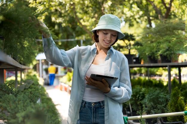 온실에서 일하는 젊은 웃는 여자