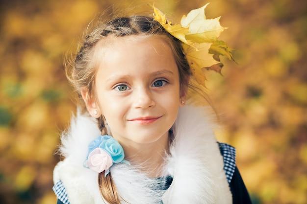 色鮮やかな紅葉と若いsmiliing少女の顔の肖像画。秋の葉の髪。秋の時間。季節と秋の休日。