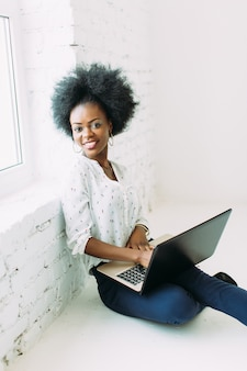 Young smiling african american business woman using the laptop, sitting on the floor
