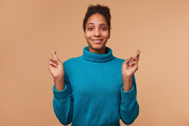 Молодая улыбающаяся афро-американская девушка с вьющимися темными волосами в синем свитере. улыбается, скрестив пальцы и надеется на удачу. изолированные на фоне biege.