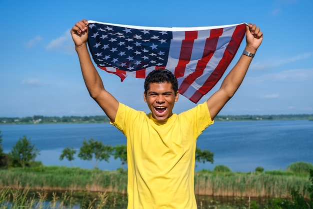 Young smiling african american man looking at camera and proudly holding waving american flag in his outstretched arms on blue sky background in summer