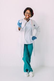 청진기를 들고 흰 코트에 젊은 웃는 아프리카 계 미국인 여자 의사