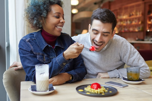 若い笑顔のアフリカ系アメリカ人女性がカフェで彼女の笑っているボーイフレンドのデザートを食べています