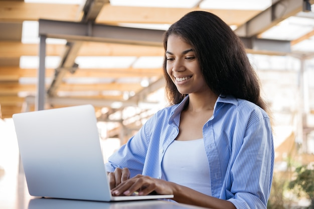 Young smiling african american woman using laptop computer working online sitting in cafe