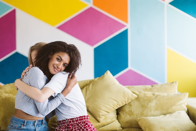 Young smiling african american woman with dark curly hair dreamily hugging girlfriend while happily  with colorful wall