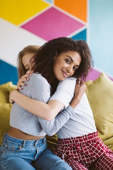 Young smiling african american woman with dark curly hair hugging girlfriend while dreamily  with colorful wall