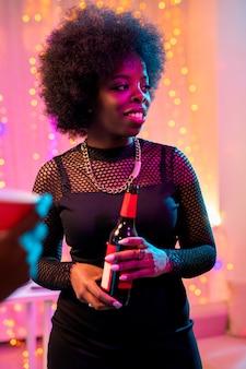 Молодая улыбающаяся африканская женщина в черной одежде держит бутылку пива, стоя среди друзей и наслаждается вечеринкой в домашней обстановке