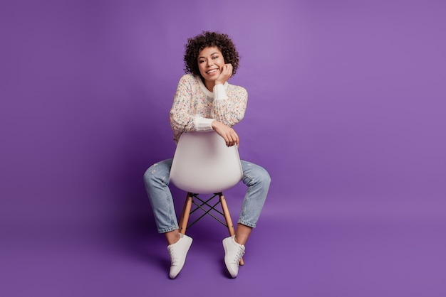 Young smiling african girl hand chik sit chair posing wear casual outfit on purple background