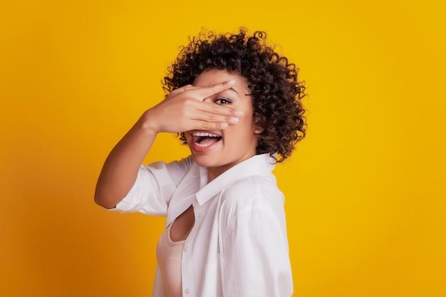 Молодая улыбающаяся африканская девушка прикрывает глаза руками, глядя сквозь пальцы, позирует на желтом фоне