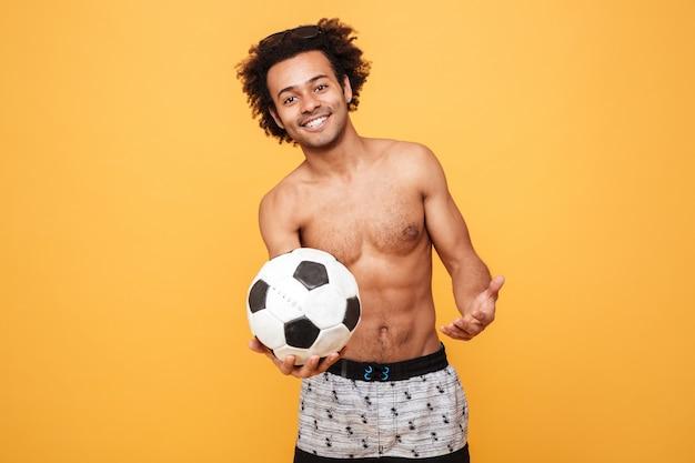 サッカーを保持している夏の服の若い笑顔アフリカ男