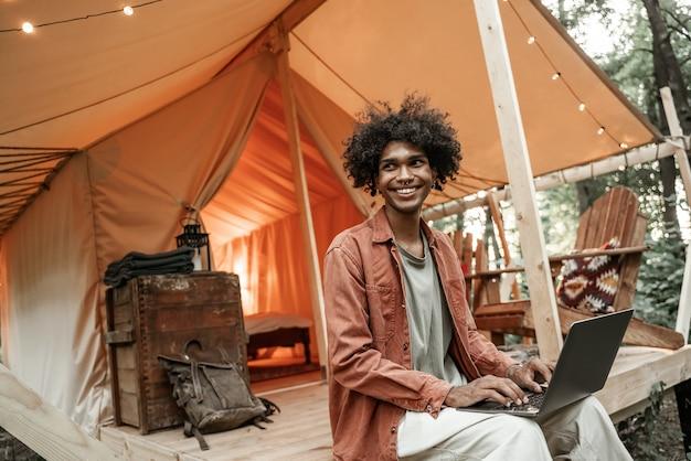 Молодой улыбающийся африканский человек с пирсингом, сидя на глэмпинге, набрав на ноутбуке. кемпинговый образ жизни. малобюджетные путешествия, отдых. wi-fi соединение, информационные коммуникационные технологии. удаленная работа
