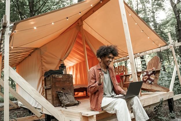 Молодой улыбающийся африканский мужчина с пирсингом разговаривает по видеосвязи на ноутбуке. кемпинговый образ жизни. малобюджетный отдых, отдых в лесу. wi-fi соединение, информационные коммуникационные технологии. удаленная работа