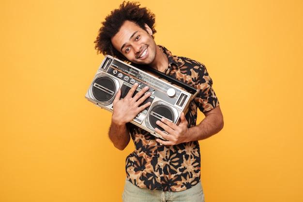 Uomo africano sorridente dei giovani con il registratore