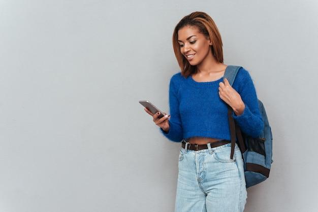 스웨터와 청바지를 입은 젊은 웃고 있는 아프리카 여성이 전화로 메시지를 작성하고 있습니다.