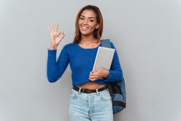 タブレットコンピューターとバックパックでセーターを着た若い笑顔のアフリカの女性は、okの兆候を示しています。孤立した灰色の背景