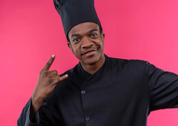 Giovane cuoco afroamericano sorridente nel segno della mano dei corni di gesti dell'uniforme del cuoco unico isolato sulla parete rosa