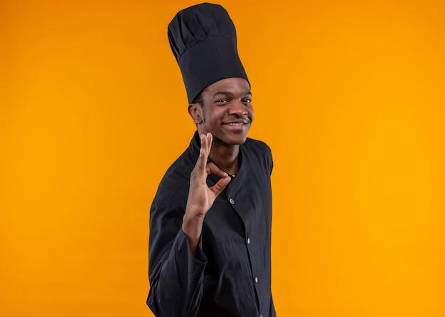 Giovane cuoco afroamericano sorridente nel segno giusto della mano di gesti dell'uniforme del cuoco unico isolato sulla parete arancio