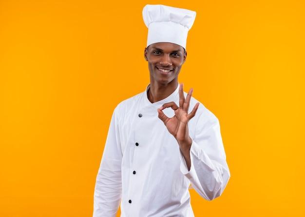 Il giovane cuoco afroamericano sorridente nei gesti uniformi del cuoco unico va bene con la mano isolata sulla parete arancio
