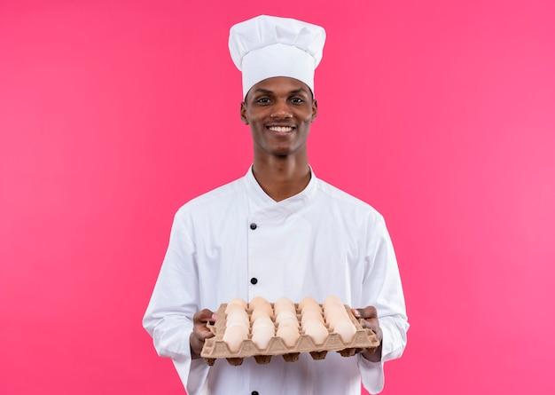 Il giovane cuoco afroamericano sorridente in uniforme del cuoco unico tiene il lotto di uova fresche isolate sulla parete rosa