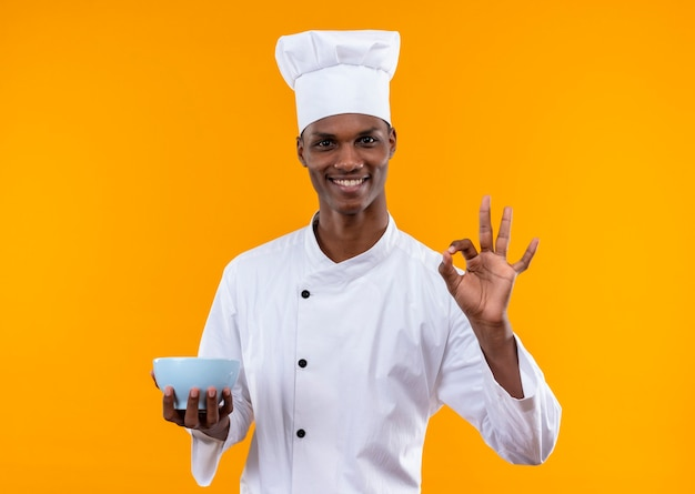 Il giovane cuoco afroamericano sorridente in uniforme del cuoco unico tiene la ciotola ed i gesti ok con la mano isolata sulla parete arancione