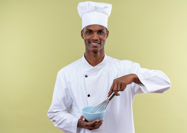 Young smiling afro-american cook in chef uniform holds bowl and whisk isolated on green wall